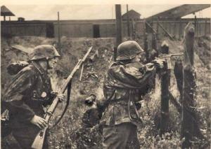 Soldados de las Waffen SS, uno de ellos apuntando con una pistola C-96.