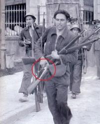 Miliciano sostiene una pistola Astra 400, tras el asalto al cuartel de la montaña al principio de la Guerra Civil, además porta fusiles mauser M1893.