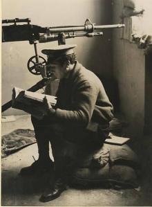 Guardia de Asalto republicano lee un libro mientras espera el ataque. Al fondo una ametralladora St. Étienne M1907.